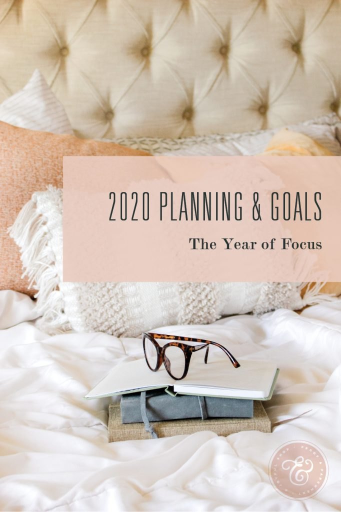 Bed with notebooks and glasses with text overlaid that says 2020 Planning & Goals: The Year of Focus