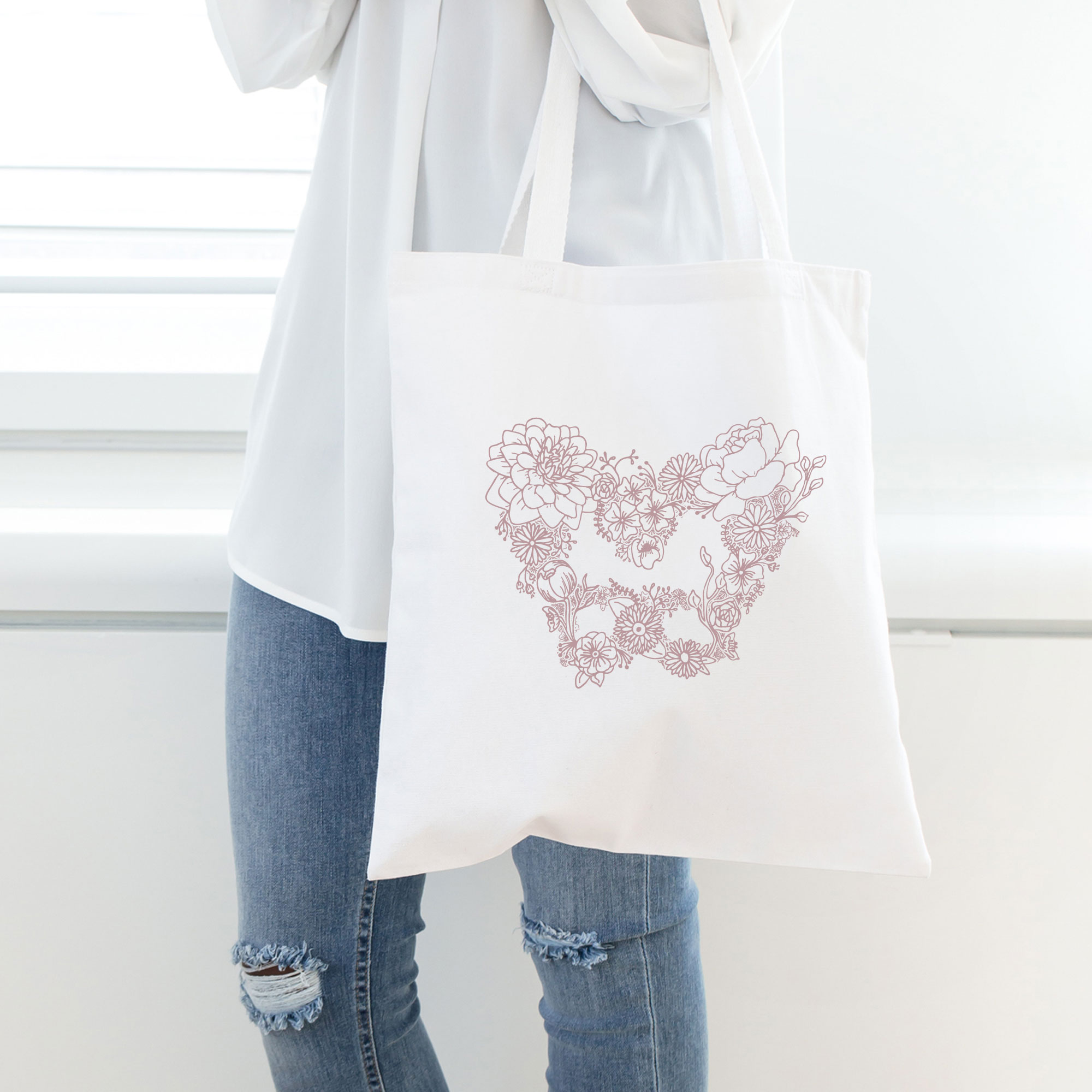 She Blooms Floral Pelvis branding icon on tote bag