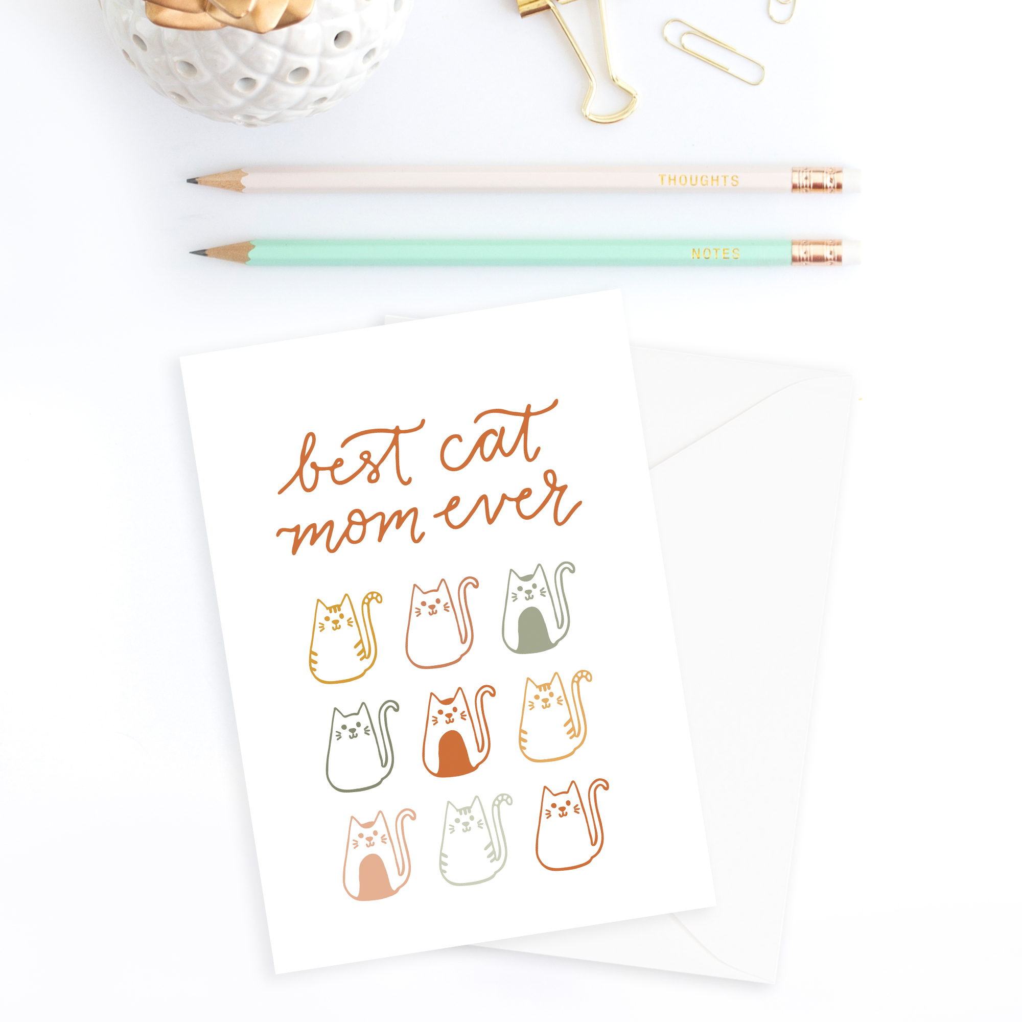 Best cat mom ever greeting card on a white background with office supplies surrounding the card